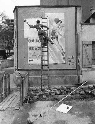 man stands on a ladder and puts up a billboard poster