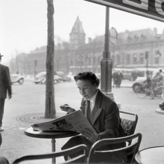 A woman drinks a coffee and reads a newspaper as she sits outside a cafe
