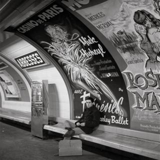 A man sits and waits on a Metro platform with a giant poster behind him